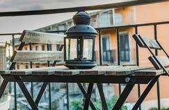 Een zwart metaal en een houten grijze lijst en twee stoelen en een oude glas en metaalkandelaar op het balkon in de ochtend royalty-vrije stock foto
