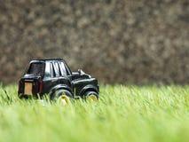 Een zwart stuk speelgoed parkeerterrein op groen grasgebied Stock Foto