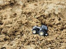 Een zwart stuk speelgoed parkeerterrein in zandbak Stock Afbeeldingen