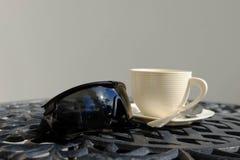 Een zwart tactisch stijl en een wit van Zonglazen een kop van koffie  royalty-vrije stock afbeeldingen