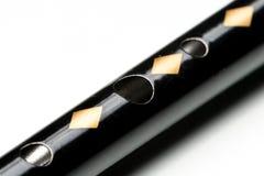 Een zwart tinfluitje die op een witte weerspiegelende oppervlakte liggen Royalty-vrije Stock Foto's