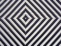Een zwart-wit diamantpatroon vormde zich in geweven plastiek als achtergrond Stock Afbeeldingen