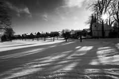 Een zwart-wit spel van schaduwen en lichten op een sneeuwvlakte Stock Foto's