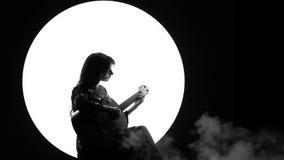 Een zwart-wit videofragment van een mooi meisje die op een klassieke gitaar tegen een witte cirkel in de rook spelen stock footage