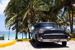 Een zwarte klassieke die auto dichtbij het strand wordt geparkeerd Royalty-vrije Stock Afbeelding