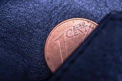 Een zwarte leerportefeuille en één cent van euro, om armoede, failliet of zuinigheid, zuinigheid en economie te symboliseren Royalty-vrije Stock Foto's