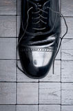 Een zwarte leerschoen met losgeknoopt kant Stock Foto