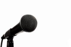 Een zwarte microfoon op wit Stock Foto