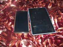 Een Zwarte telefoon en een zwarte tablet stock foto