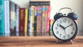 Een zwarte wekker op houten lijst met onduidelijk beeldboekenrek op achtergrond royalty-vrije stock afbeelding