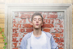 Eenage boy leaning against a wall Stock Images