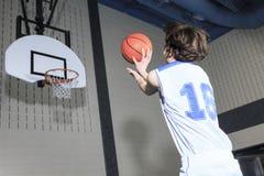 Eenager蓝球运动员戏剧他喜爱的体育 库存图片