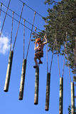 Eenager climbing a rope park, Girl climbing in adventure park Stock Images
