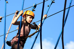 Tenager climbing a rope park, Girl climbing in adv Royalty Free Stock Photos