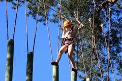 Eenager que sube un parque de la cuerda, muchacha que sube en parque de la aventura Fotos de archivo libres de regalías
