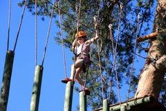 Eenager que sube un parque de la cuerda, muchacha que sube en parque de la aventura Fotos de archivo
