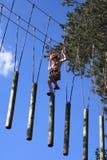 Eenager que sube un parque de la cuerda, muchacha que sube en parque de la aventura Imagenes de archivo