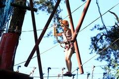 Eenager que sube un parque de la cuerda, muchacha que sube en parque de la aventura Fotografía de archivo libre de regalías