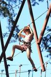 Eenager que sube un parque de la cuerda, muchacha que sube en parque de la aventura Foto de archivo