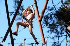 Eenager que sube un parque de la cuerda, muchacha que sube en parque de la aventura Imágenes de archivo libres de regalías