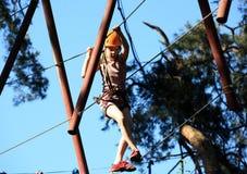 Eenager que sube un parque de la cuerda, muchacha que sube en parque de la aventura Imagen de archivo libre de regalías