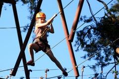 Eenager que sube un parque de la cuerda, muchacha que sube en parque de la aventura Fotografía de archivo
