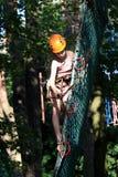 Eenager que sube un parque de la cuerda, muchacha que sube en parque de la aventura Imagen de archivo