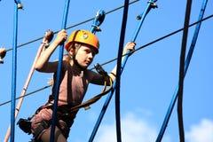 Eenager som klättrar ett rep, parkerar, flickan som klättringen i affärsföretag parkerar royaltyfria foton