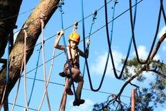 Eenager wspina się linowego parka, dziewczyny pięcie w przygoda parku Obraz Royalty Free