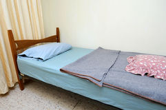 Eenpersoonsbed in motelruimte Stock Foto's