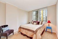 Eenvoudig beige slaapkamerbinnenland met bruin en romig tonenbed stock fotografie
