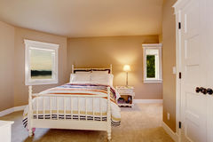 Eenvoudig beige slaapkamerbinnenland met tapijtvloer en twee vensters stock fotografie