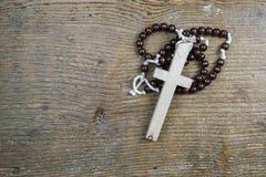 Eenvoudig Katholiek rozentuin en kruis op rustiek hout stock foto