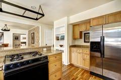 Eenvoudig keukenbinnenland met houten kabinetten en staalrefrigera Royalty-vrije Stock Afbeeldingen