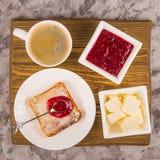 Eenvoudig ontbijt van traditionele producten - toost met boter en frambozenjam stock afbeelding