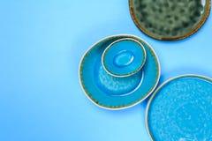 Eenvoudig rustiek met de hand gemaakt Ceramisch vaatwerk op blauwe achtergrond royalty-vrije stock afbeeldingen
