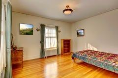 Eenvoudig slaapkamerbinnenland met hardhoutvloer stock afbeelding