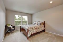 Eenvoudige beige slaapkamer met kleurrijk bed en rieten stoel stock fotografie