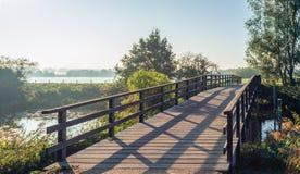 Eenvoudige houten brug met planken over een smalle Nederlandse rivier in Th royalty-vrije stock foto