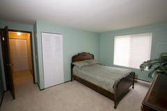Eenvoudige slaapkamer in flatgebouw met koopflats Stock Foto
