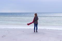 Eenzaam droevig mooi meisje die langs de kust van het bevroren overzees op een koude dag, rode hond, kip met een rode sjaal op de Royalty-vrije Stock Foto's