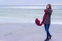 Eenzaam droevig mooi meisje die langs de kust van het bevroren overzees op een koude dag, rode hond, kip met een rode sjaal op de Stock Afbeelding