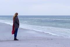 Eenzaam droevig mooi meisje die langs de kust van het bevroren overzees op een koude dag, rode hond, kip met een rode sjaal op de Royalty-vrije Stock Foto