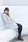 Eenzaam droevig mooi meisje in een zwarte laag en hoed, die op een witte zonnige dag van de bank koude winter een zitten Royalty-vrije Stock Afbeeldingen