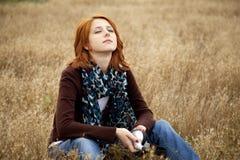 Eenzaam droevig roodharig meisje bij gebied Stock Foto's
