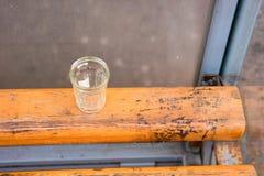 Eenzaam gefacetteerd glas bij de bushalte, concept alcoholisme royalty-vrije stock afbeeldingen