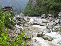 eenzaam huis bij een wilde rivier stock afbeelding