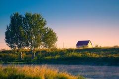 Eenzaam huis met boom op banken van rivier op een de zomerochtend met mist royalty-vrije stock afbeeldingen