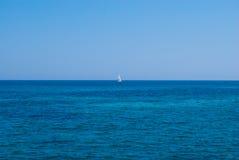 Eenzaam jacht in een open zee onder stevige blauwe hemel Stock Afbeeldingen
