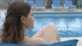 Eenzaam jong vrouwelijk zittings dichtbij zwembad, ernstig gezicht stock footage
